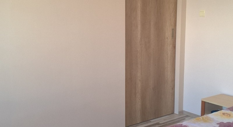 Плъзгаща врата в преградна стена от гипсокартон .